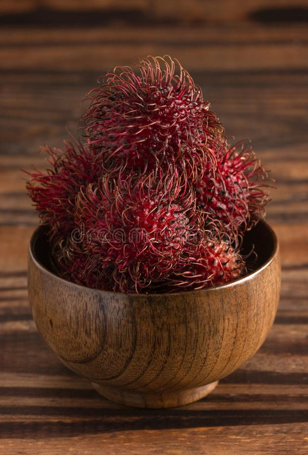 Group of Fresh Red Rambutan on a Wooden Table royalty free stock photography