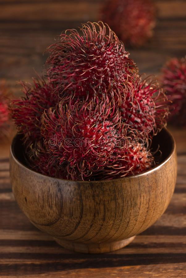 Group of Fresh Red Rambutan on a Wooden Table royalty free stock image