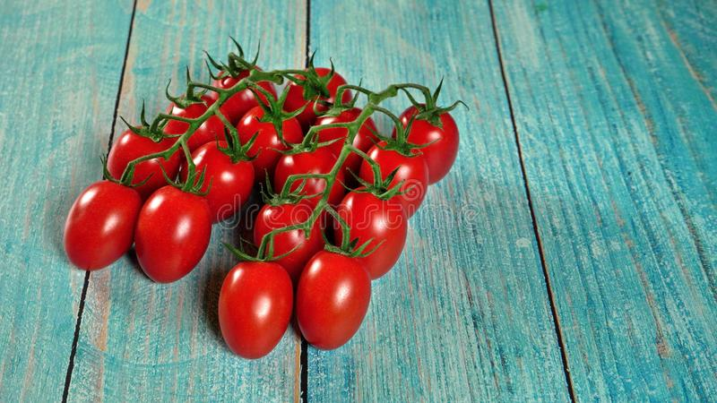 Group of fresh red tomatoes with green stem vines, on wooden boards painted blue, space for text right side stock photography