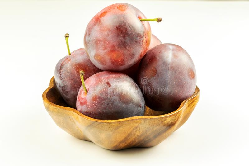 Group of fresh ripe big plums in natural wooden bowl on the white background royalty free stock image