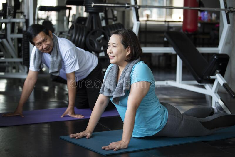 Group of friend asian senior stretching exercise at yoga gym.  elderly healthy lifestyle royalty free stock photography