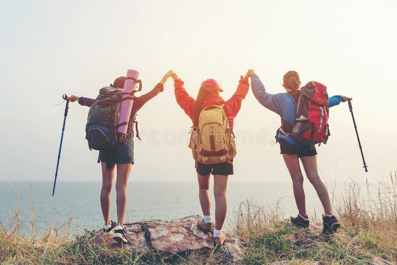 Group friend team asian young women of hikers walking adventure with backpack on a mountain at sunset. Traveler life going trip ca royalty free stock photos