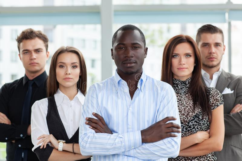 Group of friendly businesspeople with male leader in front. stock photo