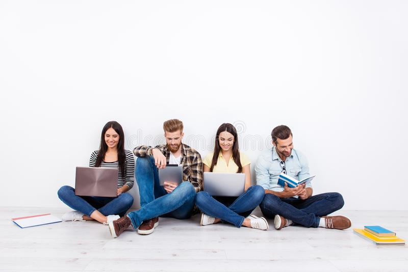 Group of friendly smiling students sitting on the floor and using modern technology for studying royalty free stock image