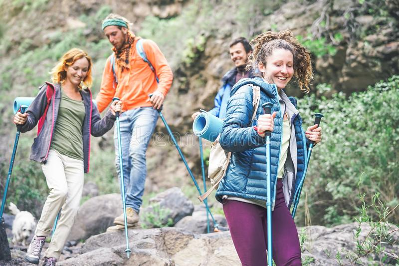 Group of friends with backpacks doing trekking excursion on mountain - Young tourists walking and exploring the nature stock photo