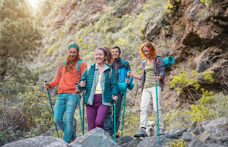 Group of friends with backpacks doing trekking excursion on mountain - Young tourists walking and exploring the wild nature stock photos