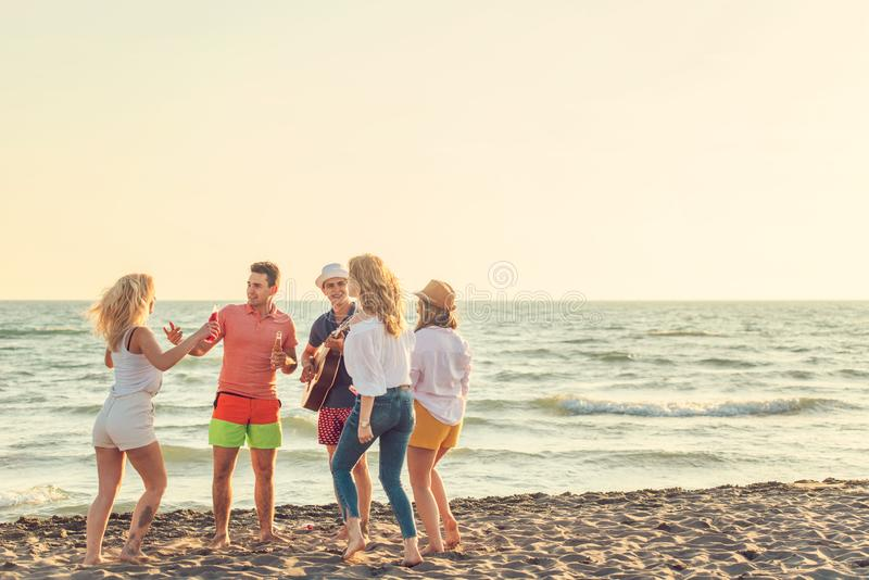 Group of friends play on the beach royalty free stock photography