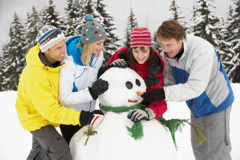 Download Group Of Friends Building Snowman On Ski Holiday Stock Photo - Image: 25645298