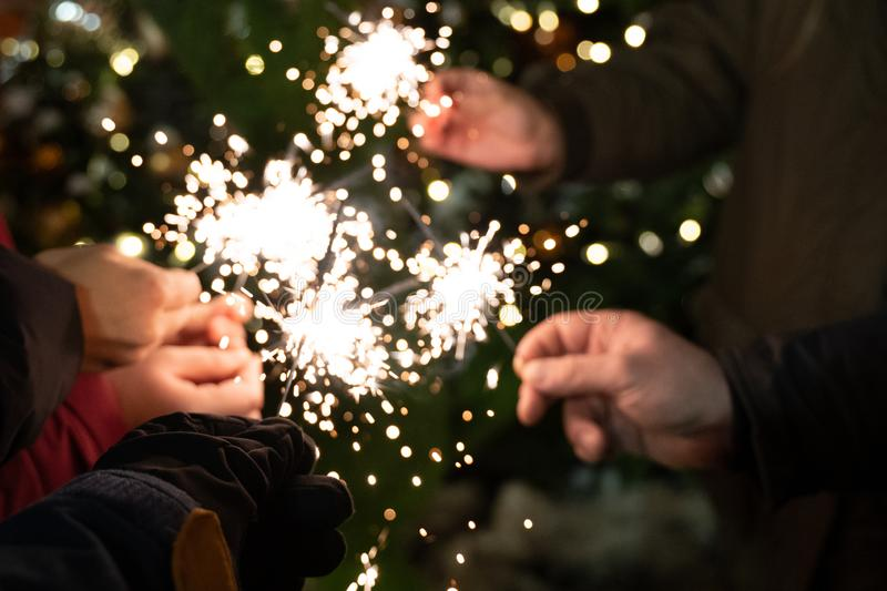 Group of friends burning Bengal lights during winter time celebrations, Christmas, New Year`s Eve royalty free stock photos
