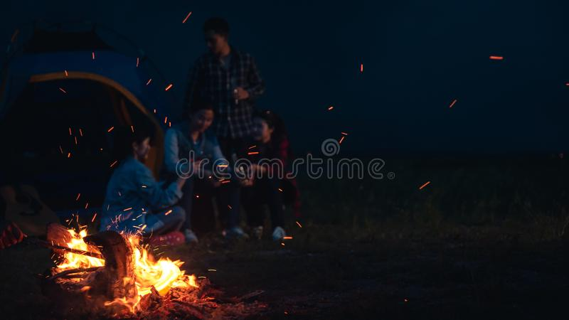Group of friends camping.They are sitting around camp fire, playing guitar and roasted sausages stock photos
