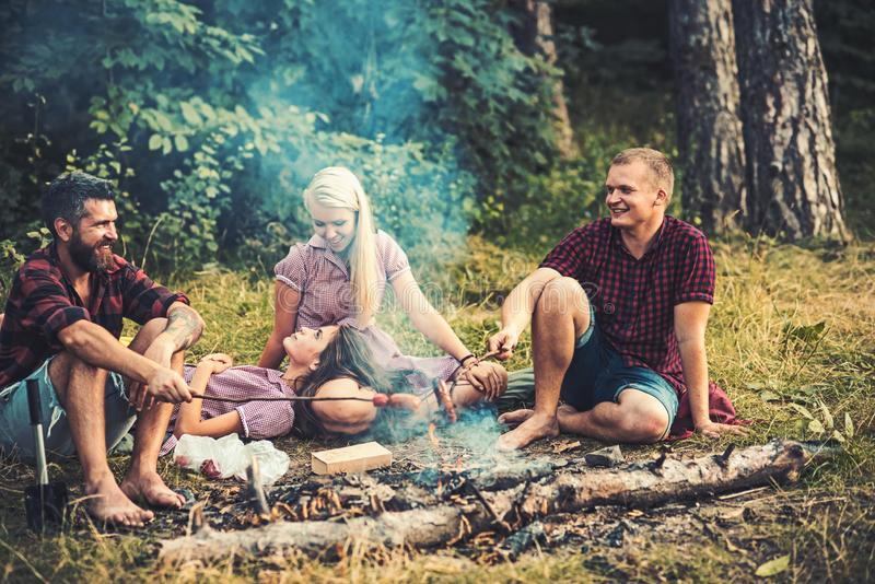 Group of friends camping in woods. Smiling people talking around campfire. Men in lumberjack shirts cooking sausages. Cheerful group of friends having picnic in royalty free stock photos