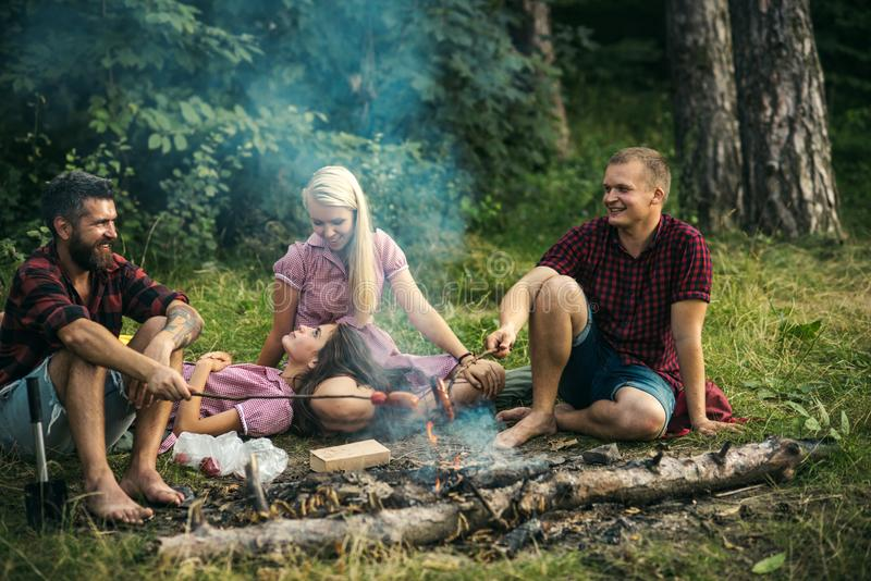 Group of friends camping in woods. Smiling people talking around campfire. Men in lumberjack shirts cooking sausages. Cheerful group of friends having picnic in stock photo