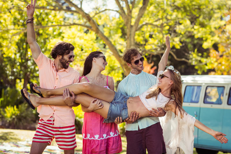 Group of friends carrying a women in park royalty free stock photography