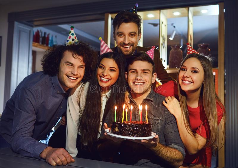 Group of friends celebrating birthday with birthday cake at restaurant stock photo