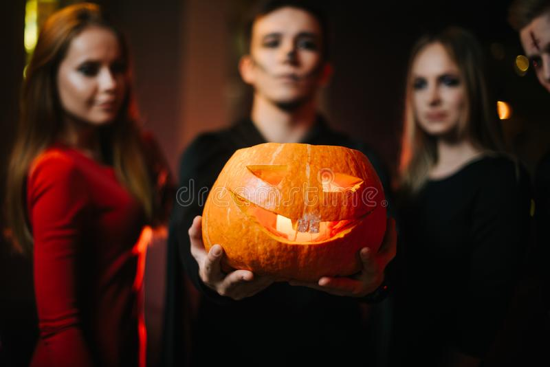 Group of friends celebrating Halloween. Guy wearing zombie costume holds pumpkin stock photos