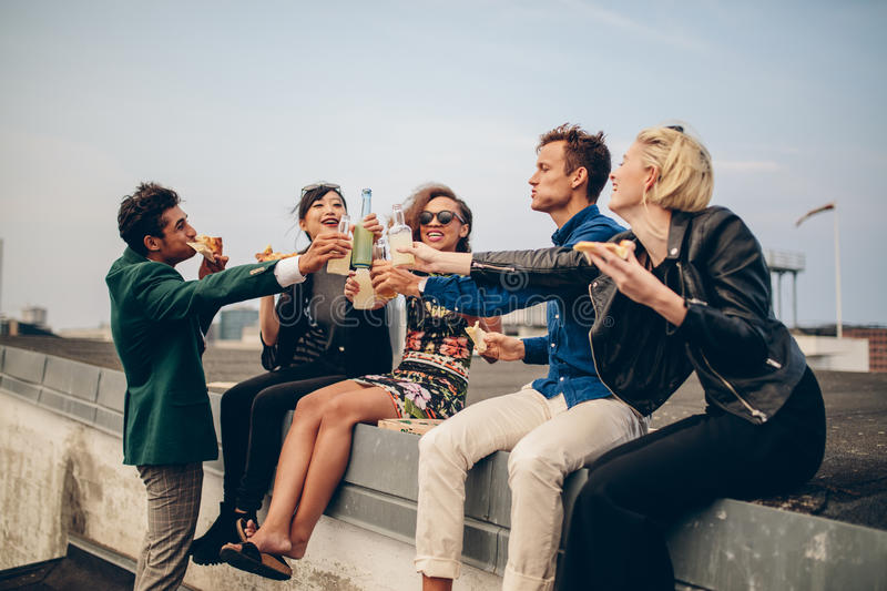 Group of friends celebrating on rooftop. Happy friends partying on the rooftop with drinks. Young men and women toasting drinks on terrace royalty free stock image