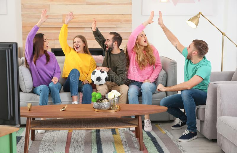 Group of friends celebrating victory of favorite soccer team royalty free stock photography