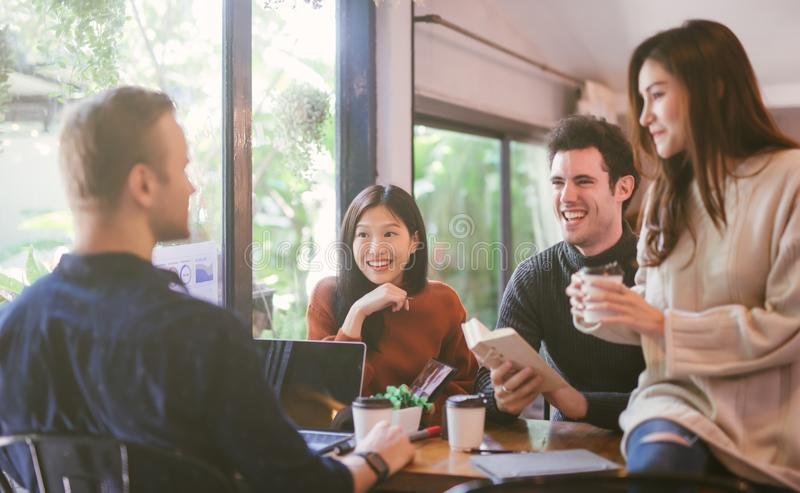 Group of friends chatting and using laptop in cafe at the coffee shop cafe in university talking and laughing together. stock image