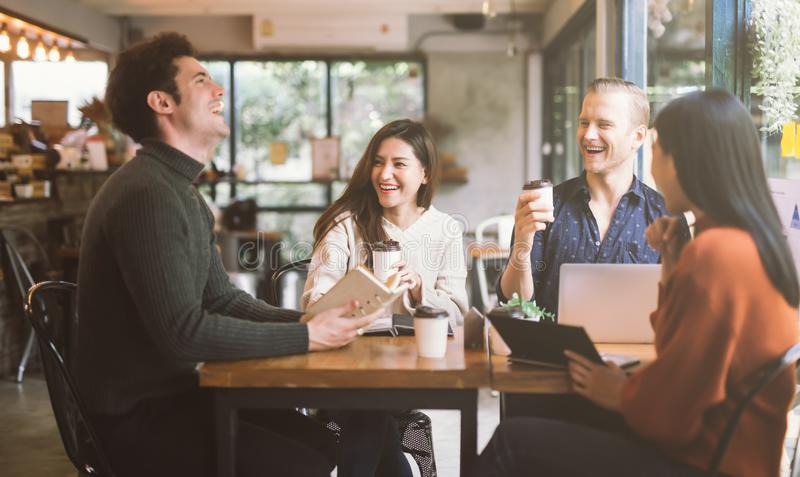 Group of friends chatting and using laptop in cafe at the coffee shop cafe in university talking and laughing together. royalty free stock images