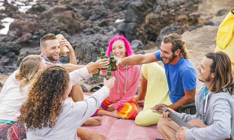 Group of friends cheering with beers on the beach - Happy people enjoying time together drinking, playing guitar stock photography