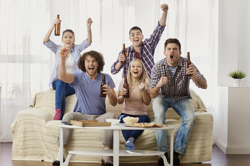A group of friends are cheering for their team watching sports T stock photography