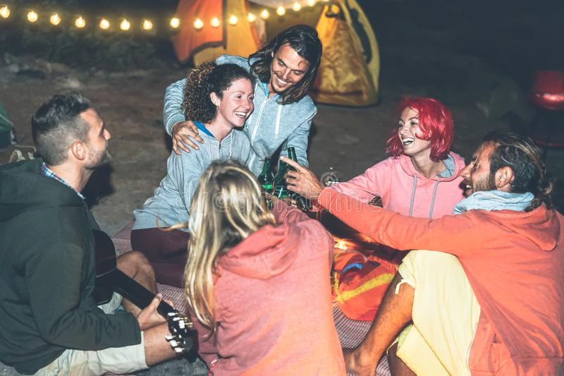 Group of friends cheering and toasting with beer while camping with tent next the beach - Happy young people having fun drinking stock image