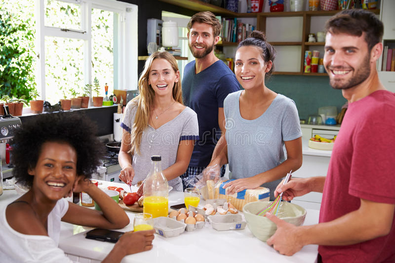 Group Of Friends Cooking Breakfast In Kitchen Together stock images