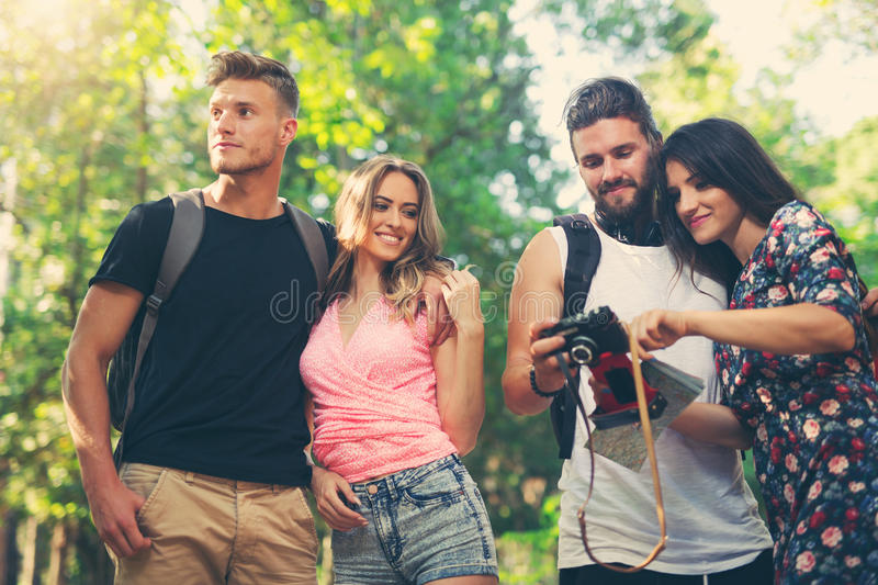 Group of friends or couples having fun with photo camera. In summer park stock photo