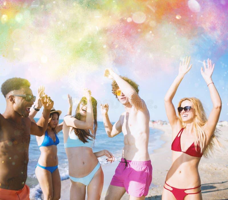 Group of friends dance under a color splash. Of powder stock image