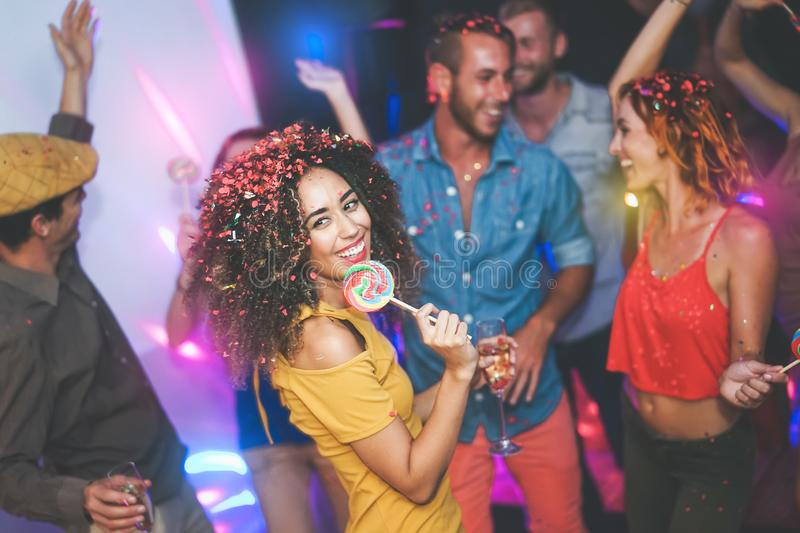 Group of friends dancing and drinking champagne at nightclub - Young happy people having fun and enjoying party eating candy royalty free stock photos
