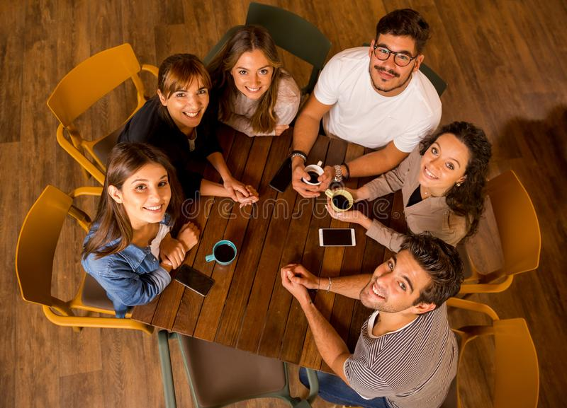Up view portrait. A group of friends drinking coffee at the cafe and looking up royalty free stock photo
