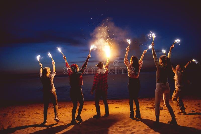 Group friends dusk signal fire beach stock images