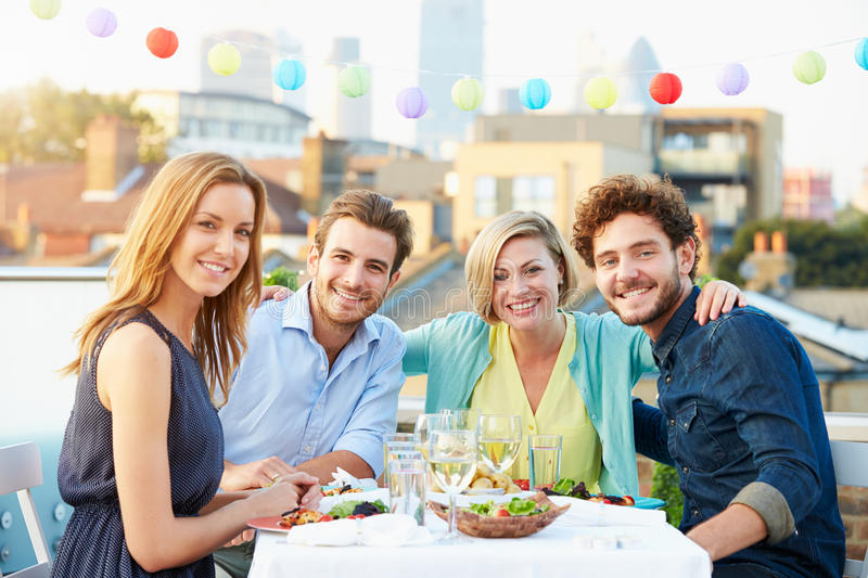 Group Of Friends Eating Meal On Rooftop Terrace stock photos