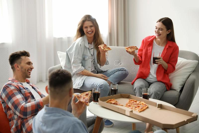 Group of friends eating tasty pizza stock photo