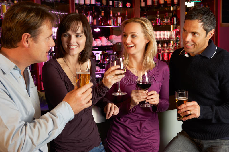 Group Of Friends Enjoying Drink Together In Bar stock image