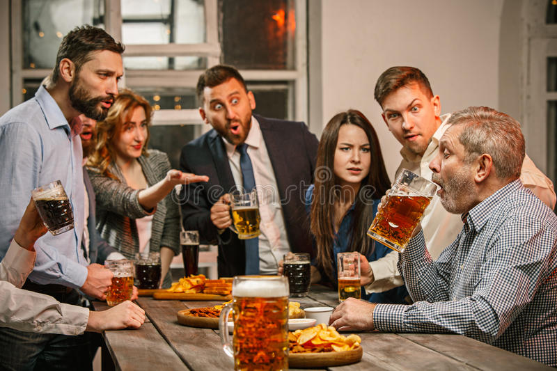 Group of friends enjoying evening drinks with beer stock photos