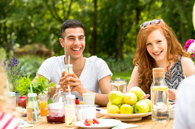 Group of friends enjoying garden party with apples on a table. Concept photo royalty free stock image