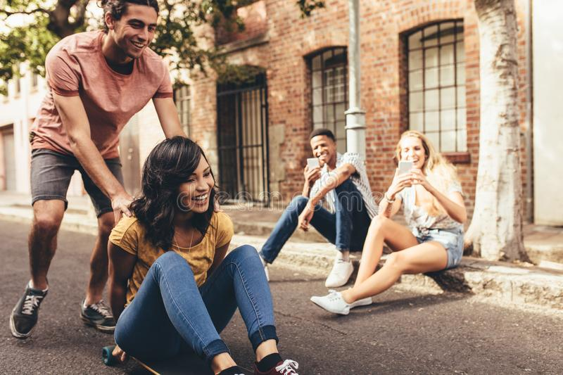 Group of friends enjoying outdoors. Young men pushing women on skateboard with their friends sitting by the road taking their pictures with mobile phone. Friends stock photos