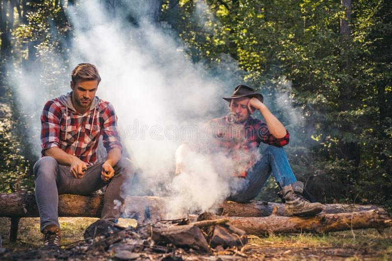 Group of friends enjoying picnic in the forest and drinking beer. Group of two male friends camping with marshmallows royalty free stock image