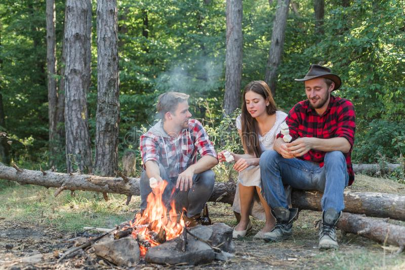 Group of friends enjoying picnic in the forest. Tourists relaxing. Happy friends enjoying bonfire in nature. Friends royalty free stock image