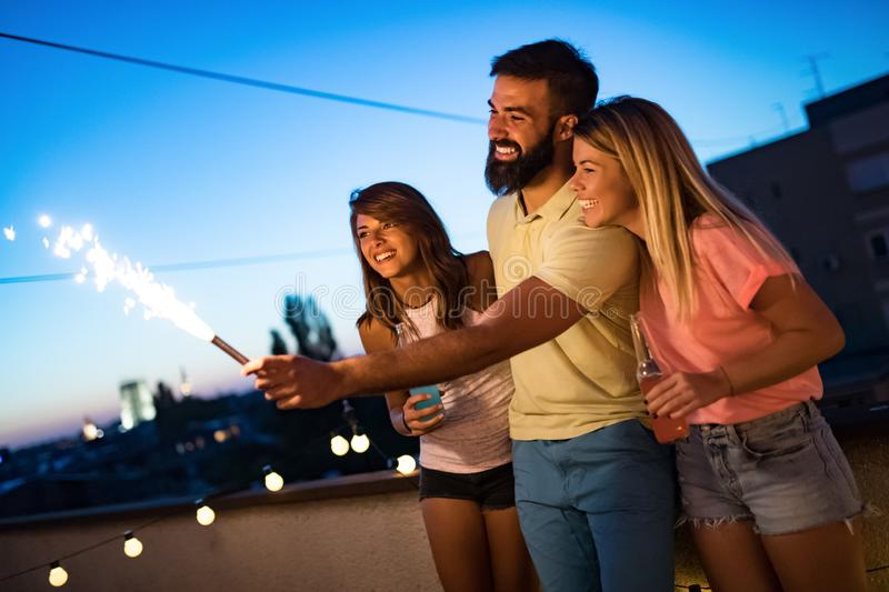 Group of friends enjoying rooftop party with sparklers stock photos