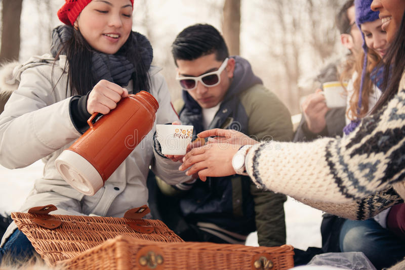 Group of friends enjoying in the snow in winter. Group of millenial young adult friends enjoying wintertime and in a snow filled park stock photo
