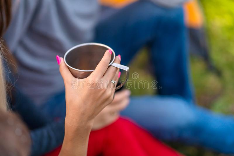 A group of friends is enjoying a warming drink from a thermos, on a cool evening by a fire in the forest. Fun time camping with stock photos