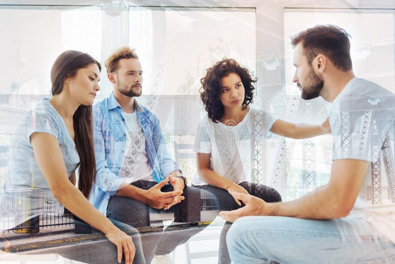 Group of friends expressing sympathy. Stuck in troubles. Waist up of best friends expressing sympathy to their friend while calming him down royalty free stock photos