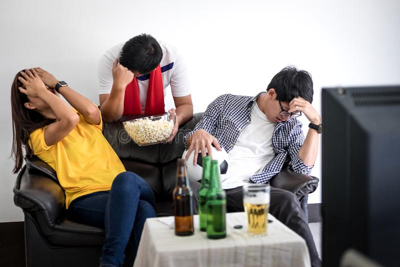 Group of friends fanclub watching soccer match on tv and cheering football team, celebrating with beer and popcorn at home, sport stock image