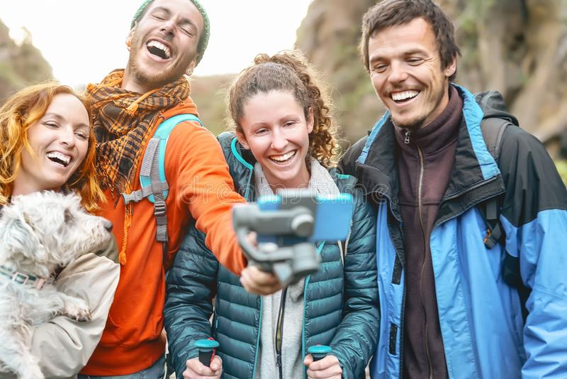 Group friends filming video with gimbal mobile smartphone while trekking mountain - Happy young people having fun stock image