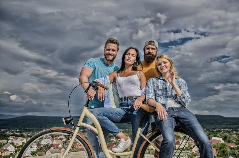 Group friends hang out with bicycle. Company stylish young people spend leisure outdoors sky background. Bicycle as best royalty free stock photography