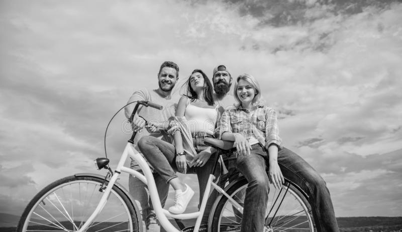 Group friends hang out with bicycle. Youth likes cruiser bike. Cycling modernity and national culture. Company stylish. Young people spend leisure outdoors sky stock images