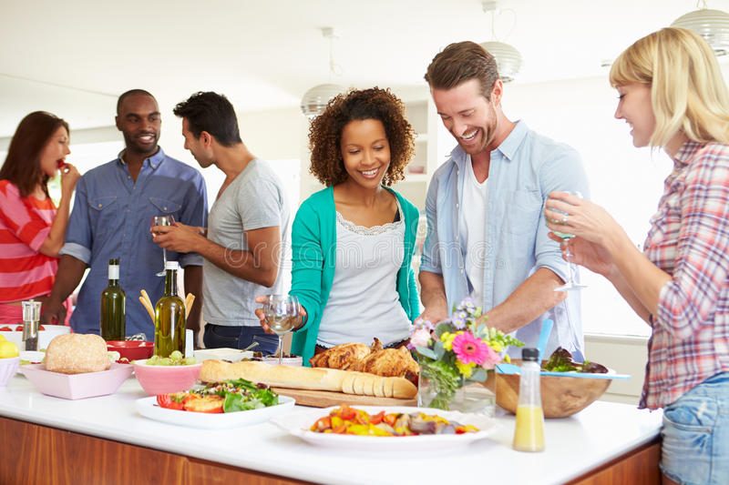 Group Of Friends Having Dinner Party At Home. In Kitchen Chatting To Each Other Whilst Eating Food stock photography