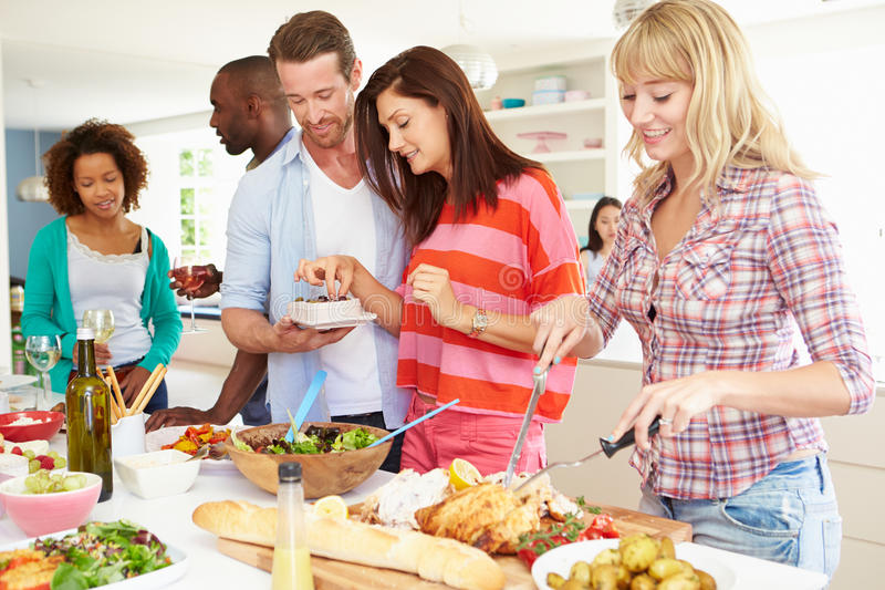 Group Of Friends Having Dinner Party At Home. In Kitchen Eating Food royalty free stock photography